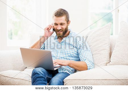Man using laptop while talking on mobile phone in living room at home