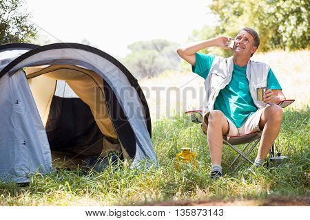 senior man is talking on the phone beside his tent