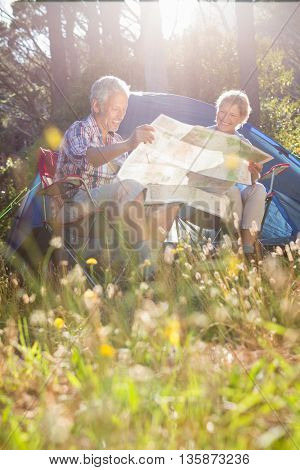 Senior couple studying the map on a camping trip