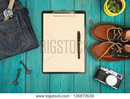 Shoes, Jeans, Clipboard, Camera, Watch And Vintage Keys On The Blue Wooden Desk