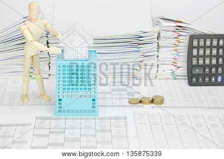 Wooden Dummy Holding House On Blue Basket With Finance Account