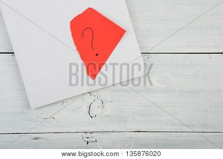 Book And Red Sheet With A Question Mark On A White Wooden Desk
