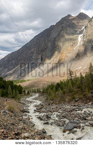 The mountain river against the woody mountains originating from a thawing glacier. Western Siberia Altai mountains.