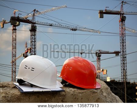 Building helmet on a background of cranes construction. Helmets orange working and white - helmet engineer. The tablet with papers. Blue sky plenty of sun
