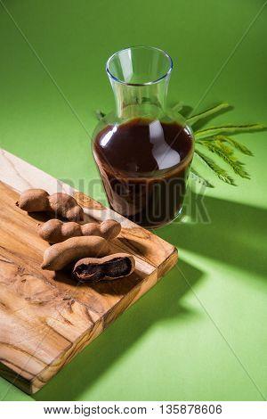 Raw tamarind fruits with sauce or puree in glass jar, imli chutney in Hindi