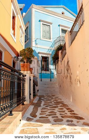 Narrow cobbled street with neo-classical houses on the Greek island of Symi.