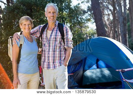 senior couple standing beside their tent in a forest