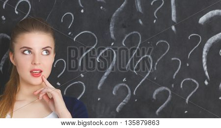 Young girl with question mark on a gray background