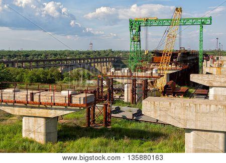 Abandoned incomplete arch bridge construction, cranes, concrete columns and rusty metal constructions