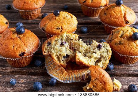 Homemade Blueberry Muffins with fresh berries on wooden table.