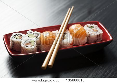 Sushi assortment on plate with chopsticks on table