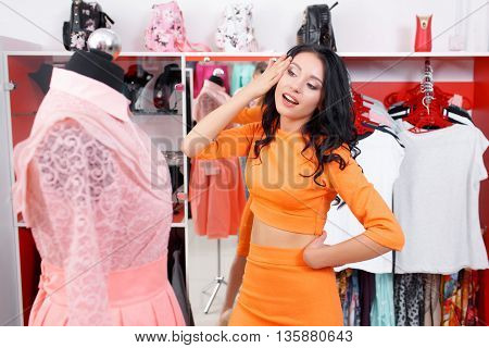 Young woman admires the dress. Woman shopping for dress in clothing retail store. Caucasian shopper girl choosing pink dress in shop during sale. Woman shopping for dress. Fashion shopping