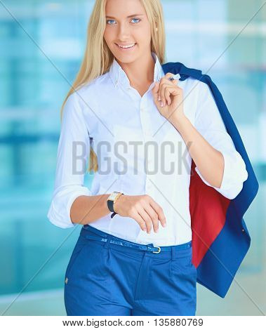 Young businesswoman standing in business center, looking on clock