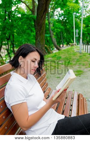 Woman is reading book. Girl with book in white polo black pant and red shoes is sitting on bench in the park is learning studying. teenager sitting outdoors with open book