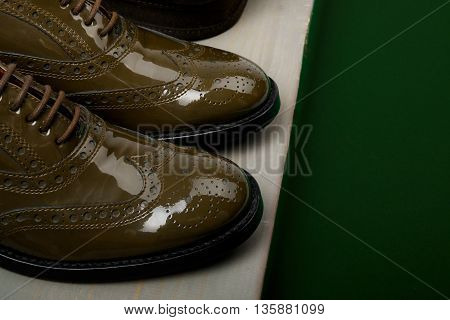 Green lacquered oxford shoes wooden background. Back view. Close up.