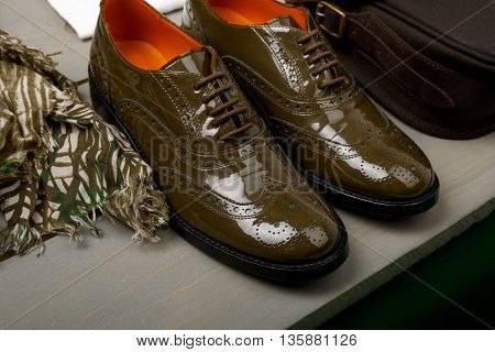 Green lacquered oxford shoes near bag and scarf on wooden background. Back view