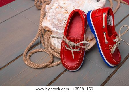 Red boat shoes on big shell and rope on wooden background. Close up.