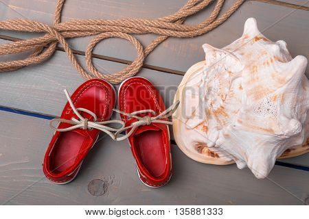 Red boat shoes near big shell and rope on wooden background. Close up. Top view.