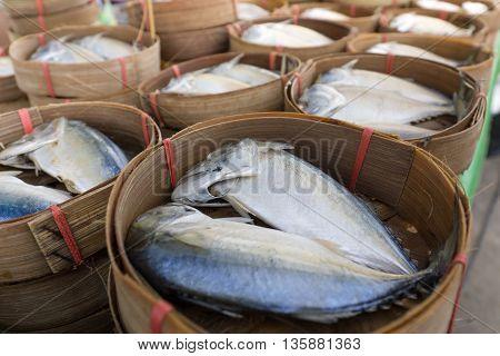 mackerels in wooden basket on wooden table