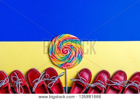 A lot of small red boat shoes near big multi-colored lollipop on colored background. Top view copy space. Frame. group of child boat shoes.