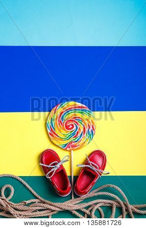 Small red boat shoes near big multi-colored lollipop and rope on colored background. Top view. Copy space frame