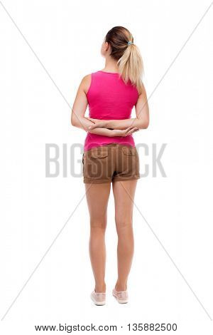 back view standing young beautiful woman. girl watching. Rear view people collection.  backside view person. Isolated over white background Blonde in brown shorts stands with his hands behind his back
