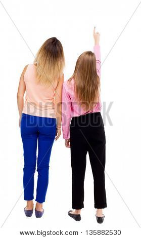 Back view of two pointing young girl. Rear view people collection.  backside view of person. Isolated over white background. The two girls looked up staring at something in the sky.