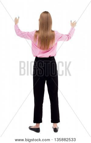 Back view of  business woman.  Raised his fist up in victory sign.    Raised his fist up in victory sign.The girl office worker in black trousers praying