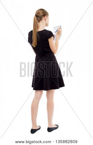back view stands woman takes notes in notebook. Rear view people collection.  backside view person. Isolated over white background. The blonde in black short dress writes something in notebook