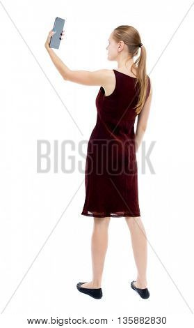back view standing young girl with tablet computer in hands of. Rear view people collection.  backside view person. Isolated over white background. blonde burgundy dress keeps self on your tablet