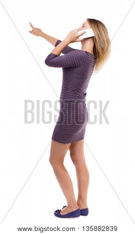 back view pointing young beautiful woman and using mobile phone. Rear view people collection. backside view person. Girl in dress standing and talking on phone and shows the distance hand