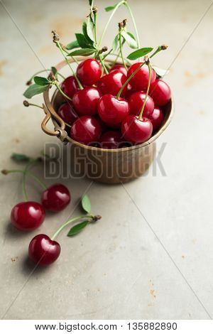 Freshly Picked Cherries With Stem And Leaves In A Copper Bowl