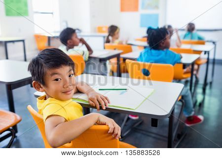 pupil sitting at his desk looking at camera in classroom at elementary school