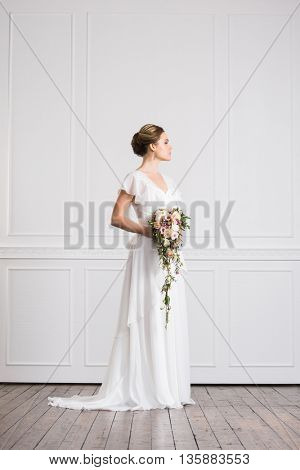 Young and beautiful bride with bouquet posing in retro interior.