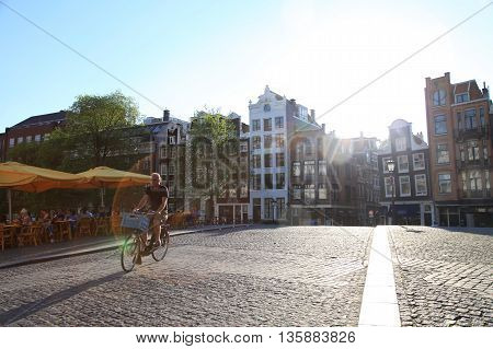 AMSTERDAM, NETHERLANDS - MAY 8, 2016: Street scene with bicycle rider on cobblestone bridge in the afternoon sunlight, Amsterdam, Netherlands.