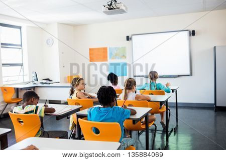 Rear view of pupils working in classroom at elementary school