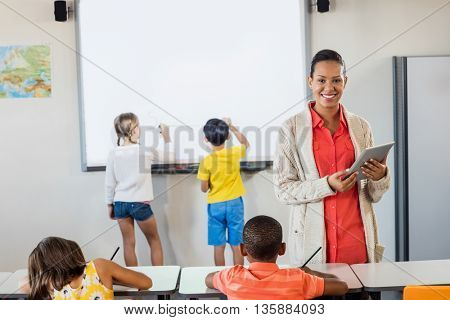 Smiling teacher using a tablet while pupils are working in classroom