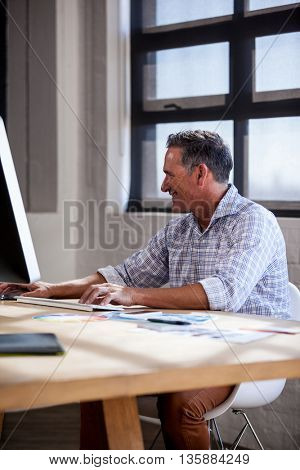 Smiling man working on computer in office