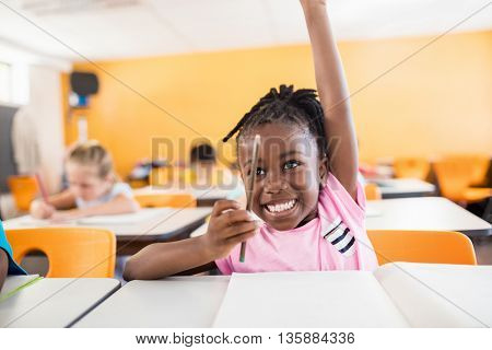 A cute pupil raising hand in classroom