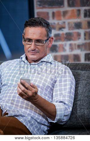 A businessman using cellphone in sofa