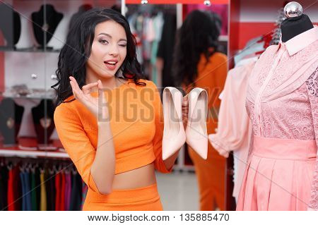 Young woman shopaholic chooses shoes to pink dress. Young woman shopping in a clothing store. Caucasian shopper girl choosing pink dress in shop during sale. Woman shopping for dress. Fashion shopping