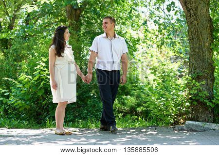 pregnant woman with husband walking in the city park, family portrait, summer season, green grass and trees