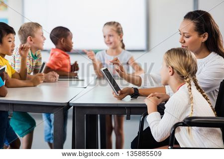 Teacher having lesson with tablet pc in classroom