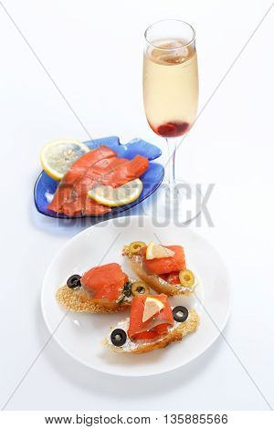 Tasty various italian sandwiches with seafood against white background. Crostini with cheese red fish fillet lemon sliced olives and glass of wine