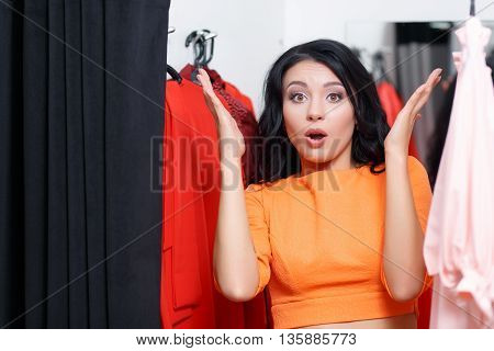 Young woman astonished in a fitting room looking at the camera. Fashionable woman shopping in a clothing store. Woman shopper in a fitting room. Woman shopping for dress. Woman shopaholic. Shopping