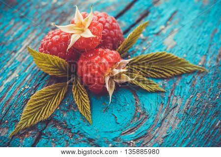 Fresh raspberry on a blue ancient wooden table