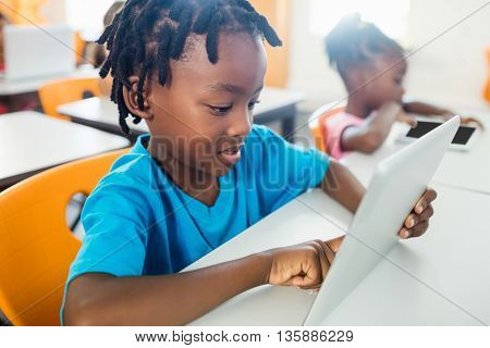 Pupil using a tablet pc in classroom at elementary school