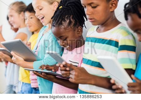 Close up view of pupils standing using tablet pc in classroom