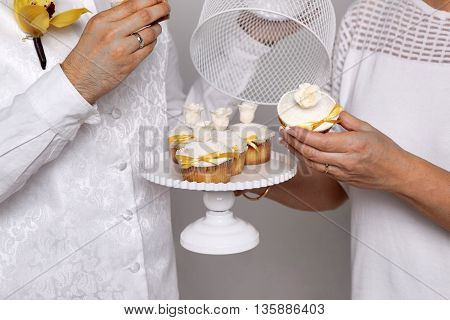 Beautiful wedding cakes in the hands of a pair