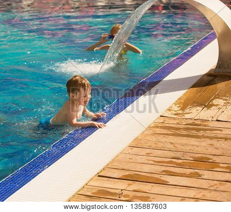 Little boy playing in swimming pool in bulgaria
